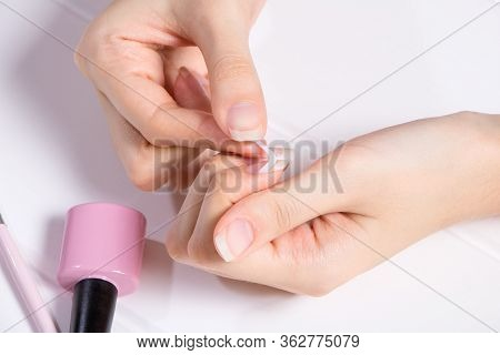Manicure. A Woman Glues Stickers On Her Nails For French Manicure. The Girl Applies Nail Polish. Nai