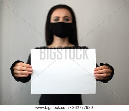 Studio Portrait Of Young Sexy Woman Wearing A Surgical Face Mask And Black Clothes Holding White Emp