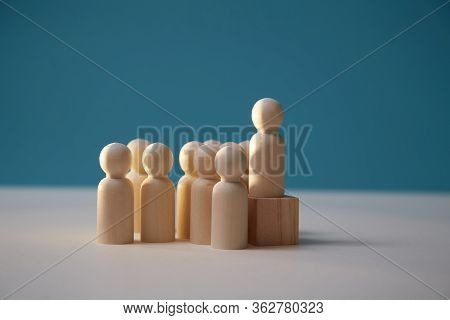 Leadership And Superiority Concept. Wooden Figure Stands On Cube. People Miniature And Leader On Dar