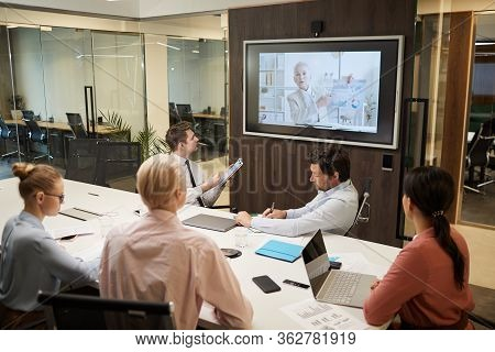 Mature Businesswoman O The Screen Holding The Online Conference For Business People Who Sitting At T