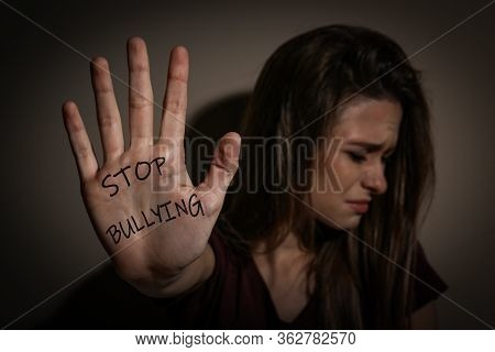 Abused Teen Girl Showing Palm With Message Stop Bullying Near Beige Wall, Focus On Hand