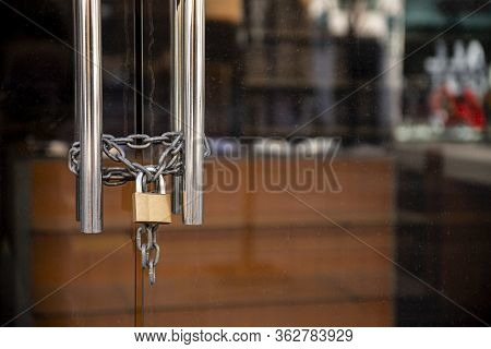 Closed Store Due To Coronavirus Pandemic. Locked Store Door With Padlock And Chains