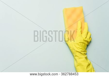 Yellow Rubber Glove Is Holding Sponge On The Bluebackground. Yellow Rubber Glove Is Cleaning With Sp