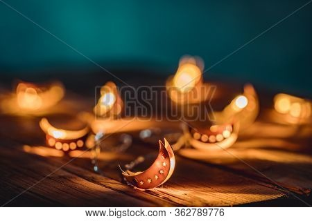 Ramadan Moon With Colorful Light Glowing At Night And Glittering With Bokeh Lights On Ground. Festiv