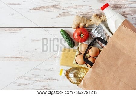 Paper Shopping Bag With Various Food. Food Donation, Safe Delivery Service Concept. Pasta, Eggs, Can