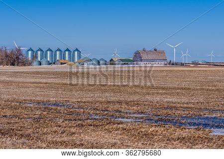 Field And Farmyard With Grain Bins And A Large Vintage Barn Surrounded By Wind Turbines In Saskatche