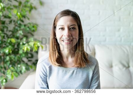 Portrait Of A Brunette Woman In Her 40s Looking At The Camera As In A Screen During A Video Call At
