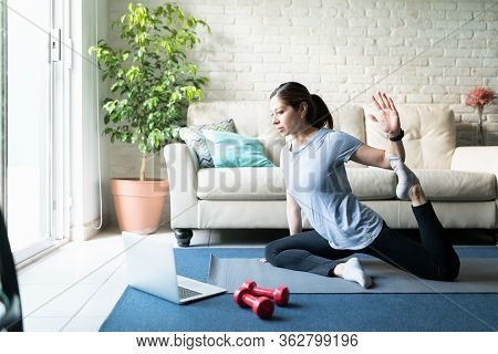 Portrait Of A Beautiful Active Woman In Her 40s Following An Online Yoga Routine And Workout At Home