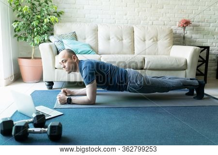 Full Length View Of An Active Caucasian Man Holding A Plank Pose While Looking At An Online Workout