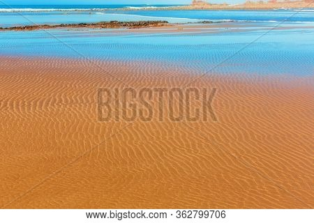 Sand Beach. Natural Patterns Background. Sand Ripples And Waves. Water On The Sand. Sunny Sea View.