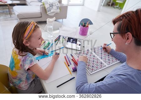 Mother and little daughter  playing together  drawing creative artwork during coronavirus quarantine measuring time on sandglass and listening music on tablet