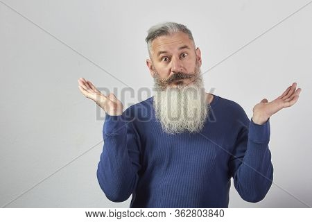 Portrait Of Perplexed Mature Gray-haired Bearded Man On Gray Background, Selective Focus