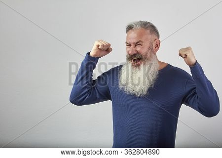 Victory Concept, Anger And Discontent, Portrait Of Mature Gray-haired Bearded Man On Gray Background