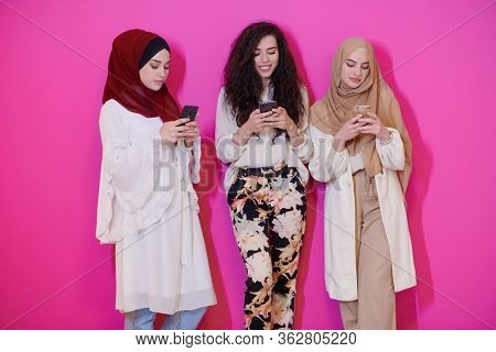 group of beautiful muslim women two of them in fashionable dress with hijab using mobile phone isolated on pink background representing modern islam fashion technology and ramadan kareem concept