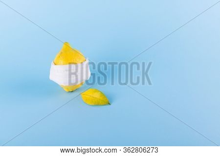 Ill Lemon In A Face Protective Mask On A Blue Pastel Background, Protection Against Coronavirus, Vir