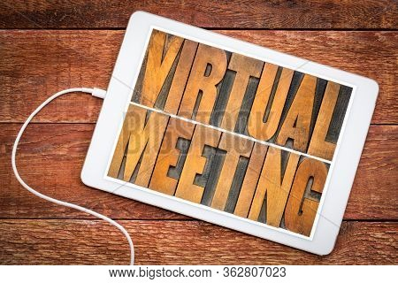 virtual meeting word abstract in vintage letterpress wood type on a digital tablet, networking and telecommunication concept