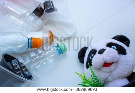 Soft Toy Panda Lies Near The Garbage On A White Background. Reusable Packaging. Disaster Of The Plan