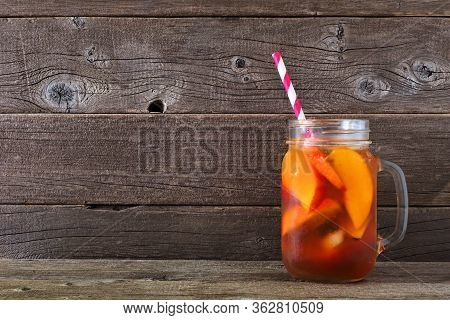 Cold Peach Iced Tea In A Mason Jar Glass. Side View Against A Rustic Wood Background.
