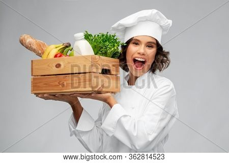 cooking, culinary and people concept - happy smiling female chef in toque holding food in wooden box over grey background