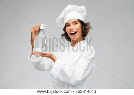 cooking, culinary and people concept - happy smiling female chef in toque with hand sanitizer or liquid soap over grey background