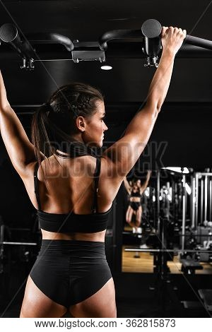 Sexy Young Fitness Girl Pulls Up In The Gym. Brunette Fitness Woman In Black Sportswear With Perfect