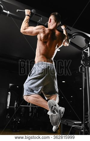 A Man Does Pull-ups On The Horizontal Bar Gym, A Dark Background, A Beautiful Body, Fitness Motivati