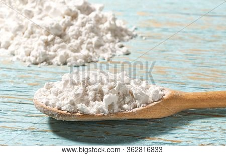 Potato Starch In Wooden Spoon With Blue Wooden Table.
