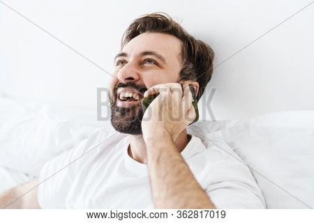 Image of young unshaven caucasian man smiling and talking on cellphone while lying in bed at home