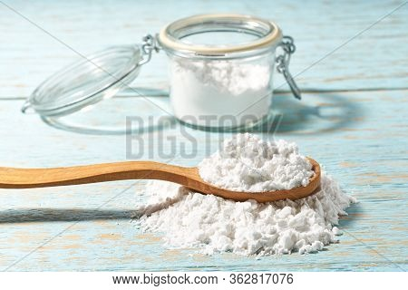 Wooden Spoon Full Of Corn Starch On A Blue Wooden Table.