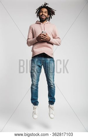 Full length portrait of a young african man wearing hoodie jumping isolated over white background, holding mobile phone