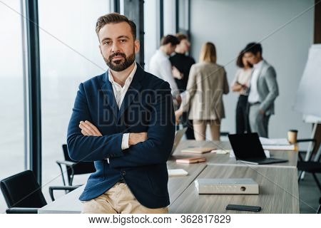 Attractive young confident businessman in formal wear sittng in the office with his colleagues on a background, arms folded