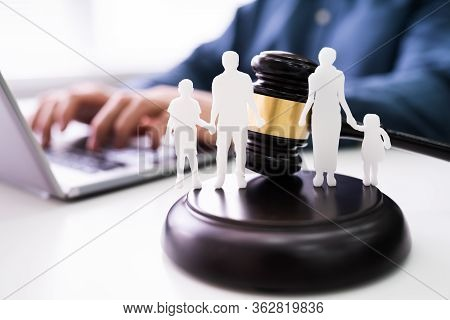 Separation Of Family Silhouette With Gavel In Courtroom