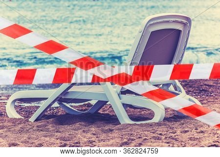 The Beach Lounger Is Blocked With A Red And White Ribbon, The Concept Of Canceling Holidays Or Cance