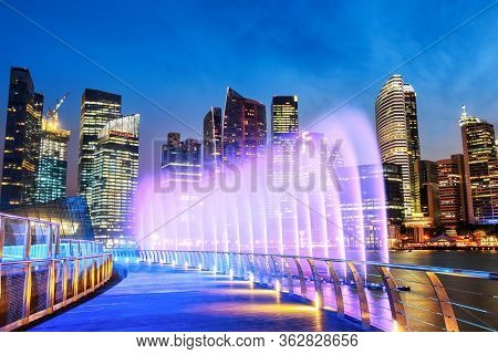 Marina Bay Fountain And Singapore Downtown Skyline At Night