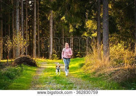 Young Woman And Dog Running Together On Country In Forest. Cheerful Female Exercising Outdoor With H