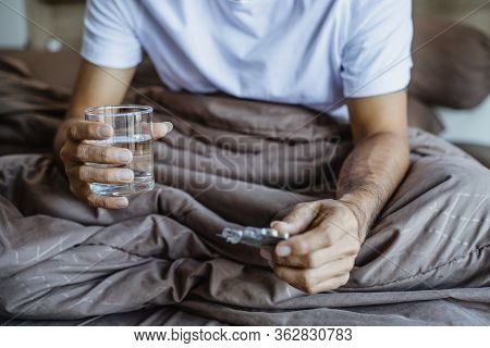 Young Man Sick Taking Medicine On The Bed, Yong Man Taking Pill And Drinking Water