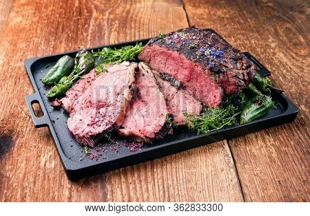 Traditional Commonwealth Sunday roast with sliced cold cuts roast beef with herbs and chili as closeup on a modern design tray