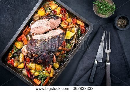 Traditional barbecue lamb roast sliced with tomatoes and fried potatoes as top view in a metal tray