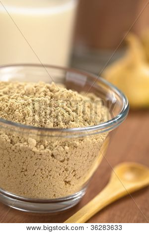 Powdered Maca or Peruvian ginseng (lat. Lepidium meyenii) in glass bowl with milk chocolate drink and maca roots in the back (Selective Focus Focus one third into the maca powder) poster