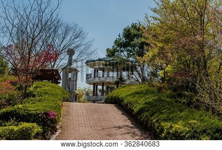 Jinan, South Korea; April 21, 2020: Concrete Monument And Three Story Pavilion At Top Of Hill In Pub