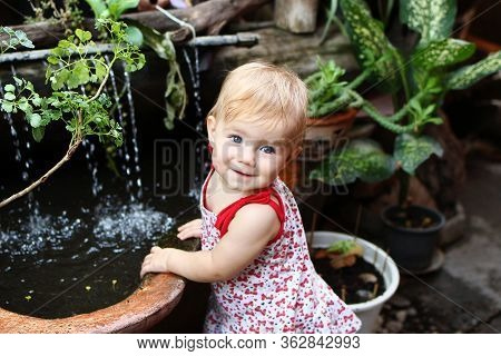 Little Smiling Girl With Blond Hair And Blue Eyes In Sundress Is Standing In Garden With Pot Plants