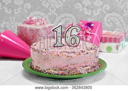 A Pretty Pink, Sprinkled Birthday Cake With The Numbers 16 On Top.  Gifts And Party Hats By Cake.