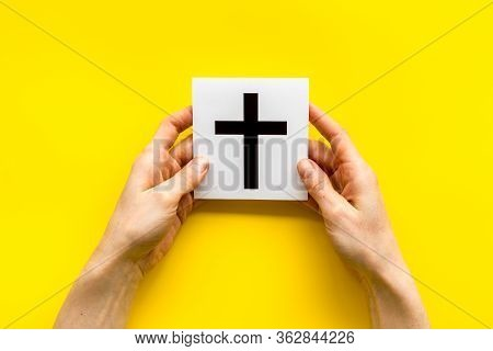 Catholic Cross Sign In Hands - Catholicism Religion Concept - On Yellow Background Top View