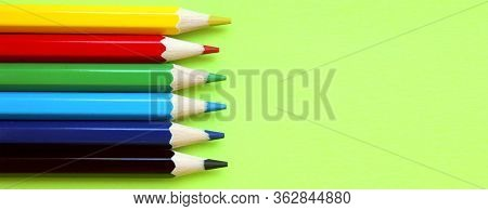 Colored Pencils On A Yellow Background. 6 Colors Black, Blue, Blue, Green, Red, Yellow. Pencils Are