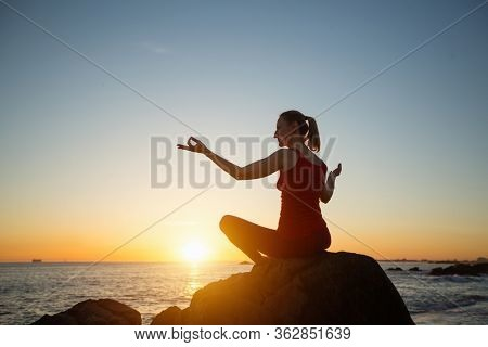 Yoga woman on the ocean coast during warm amazing sunset.