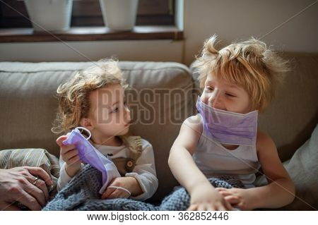 Two Small Sick Children With Face Mask At Home Sitting On Sofa.