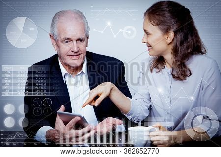 Man And Woman Using Touchpad With Virtual Business Analytics. Closeup Of Smiling Senior Businessman