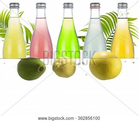 Bottles With Various Carbonated Drinks. Lemon, White Grapefruit And Avocado In The Water.