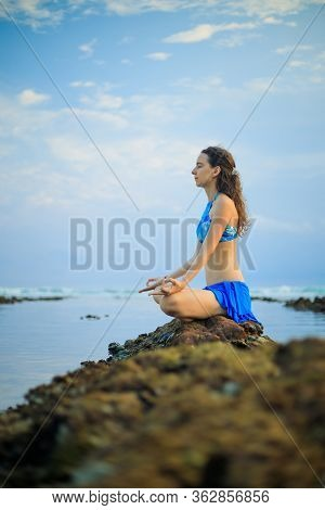 Attractive Woman, Meditating, Practicing Yoga And Pranayama At The Beach. Sunset Yoga Practice. Hand