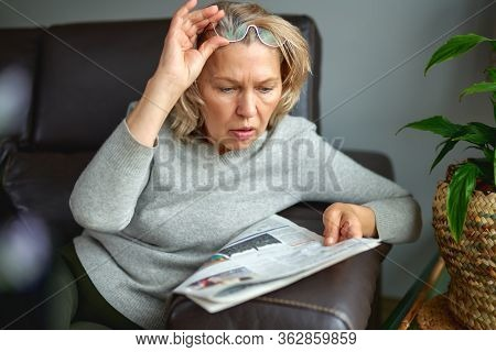 Portrait Of A Concerned Woman Reading Bad News In A Newspaper Sitting On A Couch In The Living Room